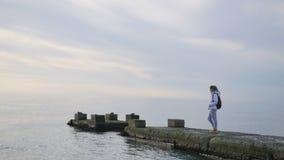Kvinna i omslagsställning på havspir som omkring ser och tycker om landskapsikt stock video