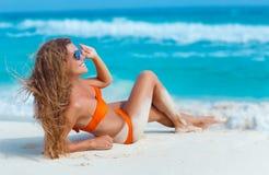 Kvinna i orange bikini på en tropisk strand fotografering för bildbyråer