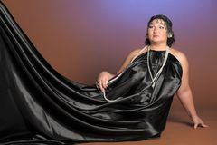 Kvinna i orientaliska ?mbetsdr?kter i svart med p?rlor arkivfoto