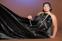 Kvinna i orientaliska ?mbetsdr?kter i svart med p?rlor royaltyfri foto