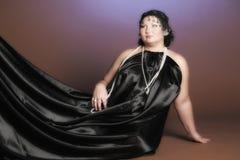 Kvinna i orientaliska ?mbetsdr?kter i svart med p?rlor royaltyfri bild