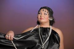 Kvinna i orientaliska ?mbetsdr?kter i svart med p?rlor royaltyfria foton