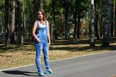 Kvinna i overaller som står i parkera Arkivbild