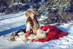 Kvinna i pälsväst och en röd kjol som spelar med hunden i snön Royaltyfri Bild