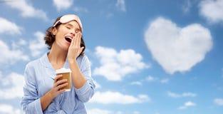 Kvinna i pajama- och ?gonmaskering med att g?spa f?r kaffe arkivfoton