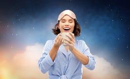 Kvinna i pajama och sovamaskering som dricker kaffe royaltyfri foto