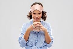Kvinna i pajama och sovamaskering som dricker kaffe arkivbild