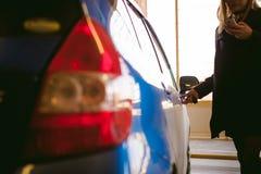 Kvinna i parkeringsplats på blå bilbakgrund Öppnar dörren med tangent Royaltyfria Bilder