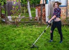 Kvinna i plädskjorta som mejar gräsmatta fotografering för bildbyråer
