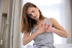 Kvinna i pyjamas som har hjärtinfarkt Arkivbild