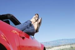 Kvinna i röd cabriolet med ben som ut klibbar Royaltyfria Bilder