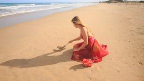 Kvinna i röd förälskelse för Squatsattraktionord på våt sand för strand lager videofilmer