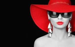 Kvinna i röd hatt och solglasögon över svart Arkivfoto