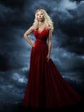 Kvinna i röd klänning, lång hårblondin i ove för modeaftonkappa Royaltyfri Bild