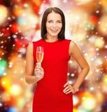 Kvinna i röd klänning med ett exponeringsglas av champagne Arkivfoto