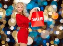 Kvinna i röd klänning med ordförsäljning på shoppingpåse royaltyfri bild