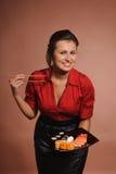 Kvinna i röd klänning med pinnar och plattan av sushi Arkivbild