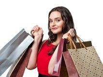 Kvinna i röd klänning med shoppingpåsar Arkivfoto