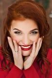 Kvinna i röd klänning och röd läppstift på hennes kanter som in camera ler och ser Arkivbilder