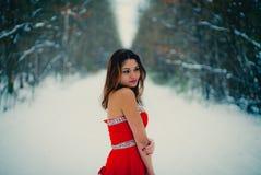 Kvinna i röd klänning Sibirien vinter i skogen som mycket är kall fotografering för bildbyråer