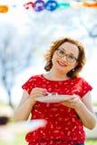 Kvinna i röd klänning som äter på trädgårdpartiet fotografering för bildbyråer