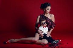 Kvinna i röd kort klänning med ett pojkebarn Arkivbilder