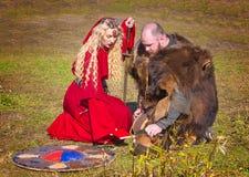 Kvinna i röd medeltida kläder och riddaren Royaltyfri Foto