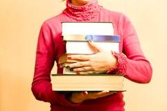 Kvinna i röd tröja med böcker i hand Royaltyfri Bild