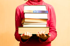 Kvinna i röd tröja med böcker i hand Fotografering för Bildbyråer