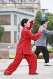 Kvinna i röda praktiserande Tai Chi, Yangzhou, Kina arkivbild