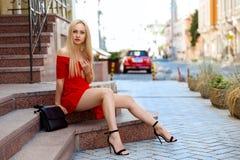Kvinna i rött klänningsammanträde på trappan Arkivfoton