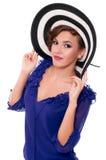 Kvinna i randig bredbrättad hatt Arkivfoto