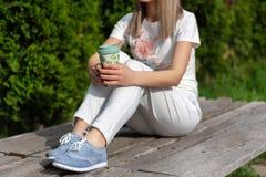 Kvinna i randiga flåsanden, blåa gymnastikskor och t-skjortan som sitter på bänken och rymmer koppen kaffe och att vila arkivfoton