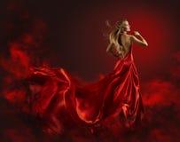 Kvinna, i röd klänning, damen Fantasy Gown Flying och att vinka Royaltyfri Foto