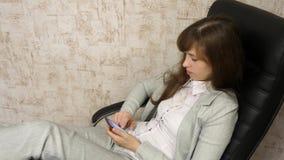 Kvinna i regeringsst?llning som vilar i arbetsplats den h?rliga aff?rskvinnan med telefonen sitter i en stol med kal fot p? tabel arkivfilmer