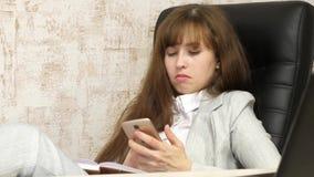 Kvinna i regeringsst?llning som vilar i arbetsplats den h?rliga aff?rskvinnan med telefonen sitter i en stol med kal fot p? tabel lager videofilmer