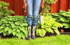 Kvinna i regnkängor i trädgård royaltyfria foton