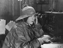 Kvinna i regnrocken som överför meddelandet i morsealfabet (alla visade personer inte är längre uppehälle, och inget gods finns L Arkivbild