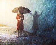 Kvinna i regnstorm med skugga arkivfoto