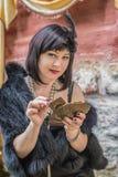 Kvinna i retro stilhåll som spelar kort Royaltyfria Foton