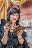 Kvinna i retro stilhåll som spelar kort Arkivbilder