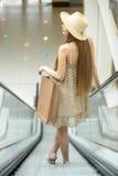 Kvinna i ridning för shoppingmitt på rulltrappan tillbaka sikt royaltyfri bild