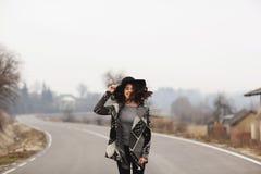 Kvinna i ritter för en härlig grå kofta och för svart hatt längs vägen royaltyfri fotografi