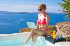 Kvinna i rosa bikini genom att använda bärbara datorn Royaltyfria Bilder