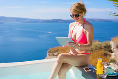 Kvinna i rosa bikini vid pölen genom att använda minnestavlan Royaltyfri Foto