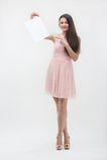 Kvinna i rosa färgklänning som pekar på ställekopia Arkivfoton