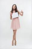 Kvinna i rosa färgklänning som pekar på ställekopia Arkivfoto