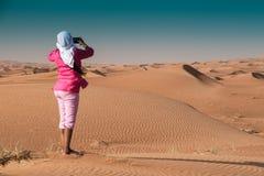 Kvinna i rosa tagande bild i den Emirati öknen av Sharjah som bär Ghutia arkivbild