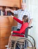 Kvinna i rullstol och åldringman Arkivbild