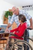 Kvinna i rullstol och åldringman Arkivfoto